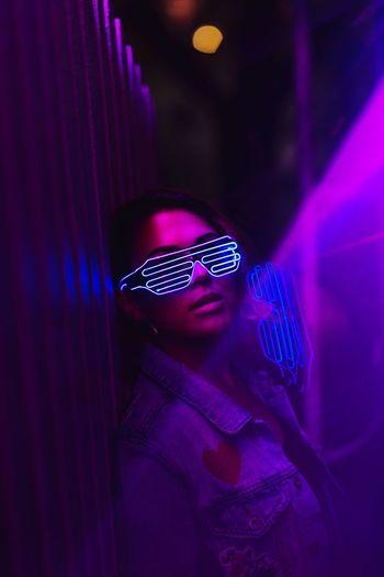 Portrait of woman wearing illuminated sunglasses at nightclub