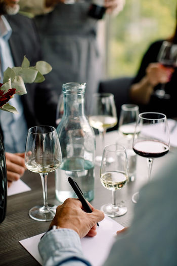 Midsection of man drinking glass on table at restaurant