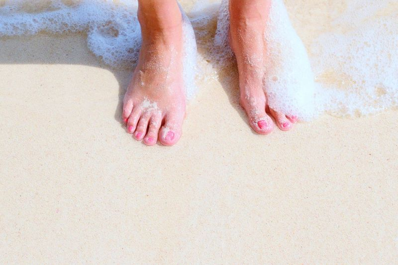Low Section Of Woman On Wet Sand At Beach