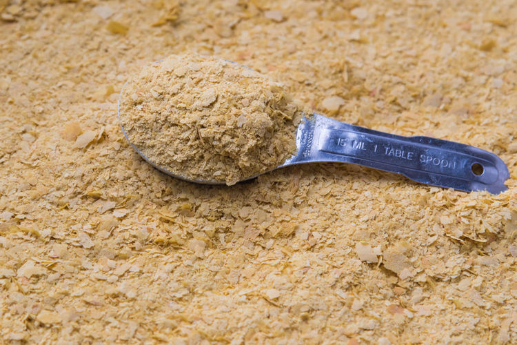 Full frame close-up vegan nutritional yeast with stainless steel tablespoon Cheese Alternative Cheese Flavour Cheese Flavour Cheese Substitute Close-up Dairy Allergy Dairy Alternative Dairy Free Dairy Substitute Deactivate Yeast Flakes Flavouring Food Full Frame Healthy Ingredient Lactose Intolerance Milk Allergy Nooch Nutritional Yeast Stainless Steel  Still Life Tablespoon Vegan Yeshi