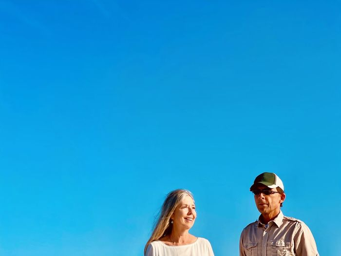 Active senior couple walking together against blue sky. front view shoulders up and copy space.