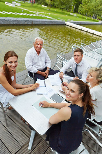 Portrait Of Smiling Colleagues Sitting With Data On Table By Pond