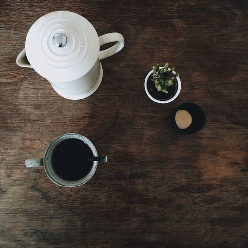 High Angle View Of Black Coffee With Tea Container On Wooden Table
