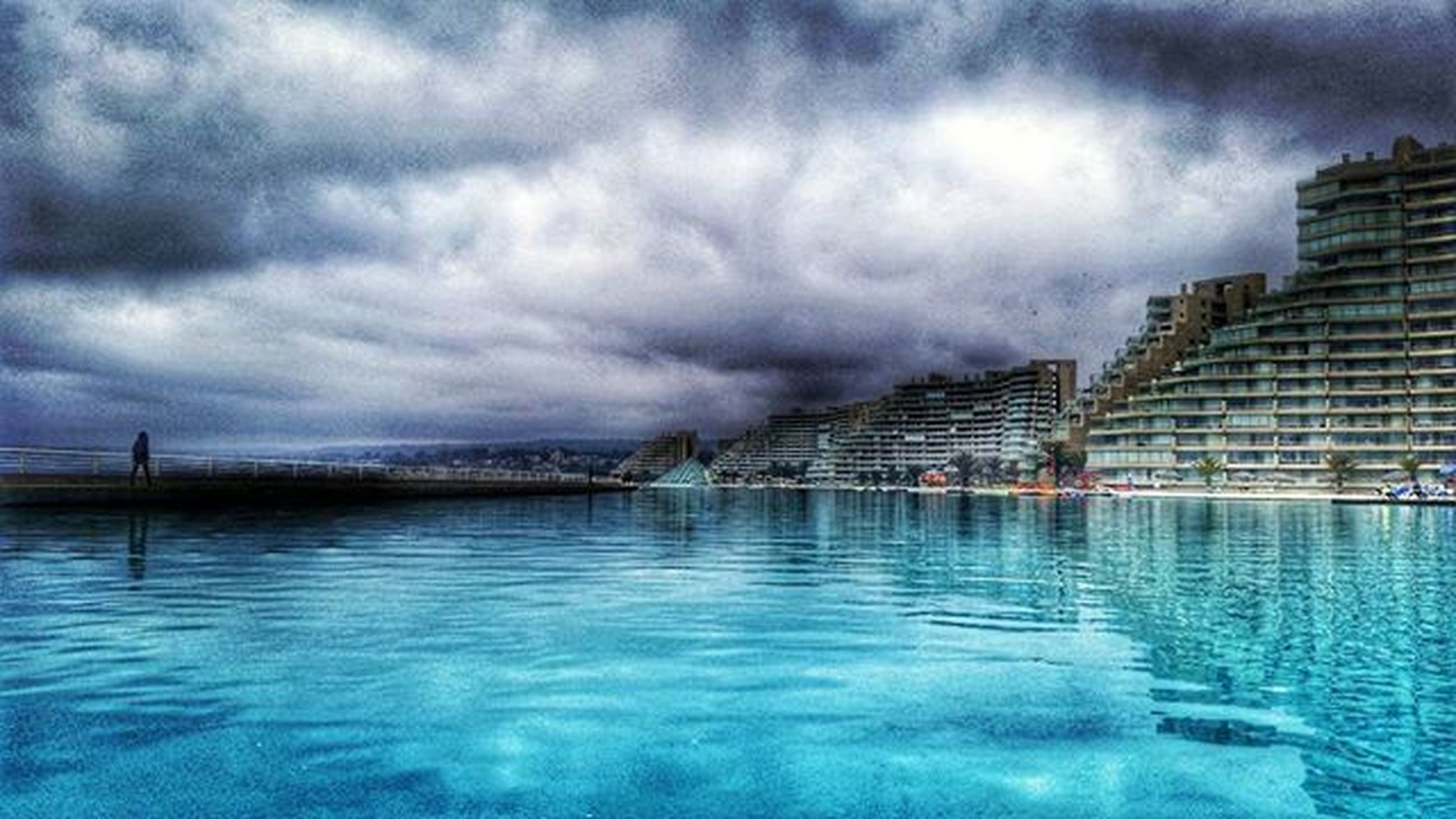 water, sky, architecture, waterfront, built structure, cloud - sky, building exterior, cloudy, weather, cloud, reflection, city, river, overcast, sea, rippled, storm cloud, dusk, nature, outdoors