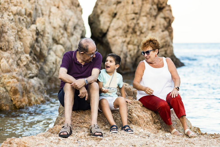 Full length of grandparents and grandson at beach