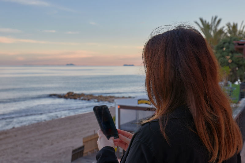 Rear view of woman using mobile phone at beach