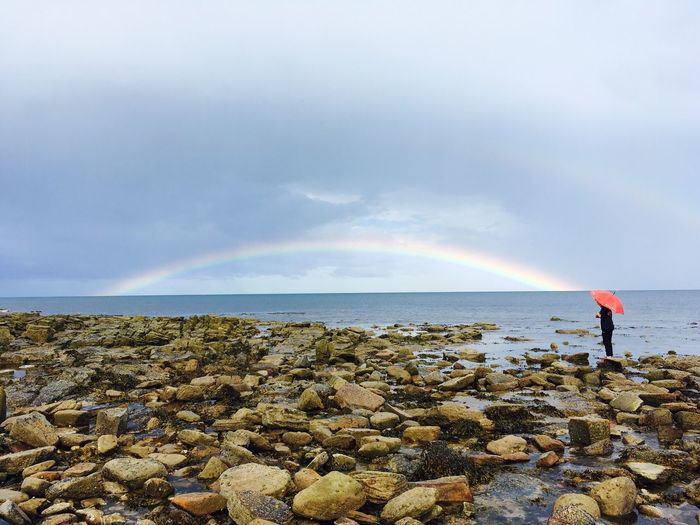 Person standing by sea with rainbow against sky during rain