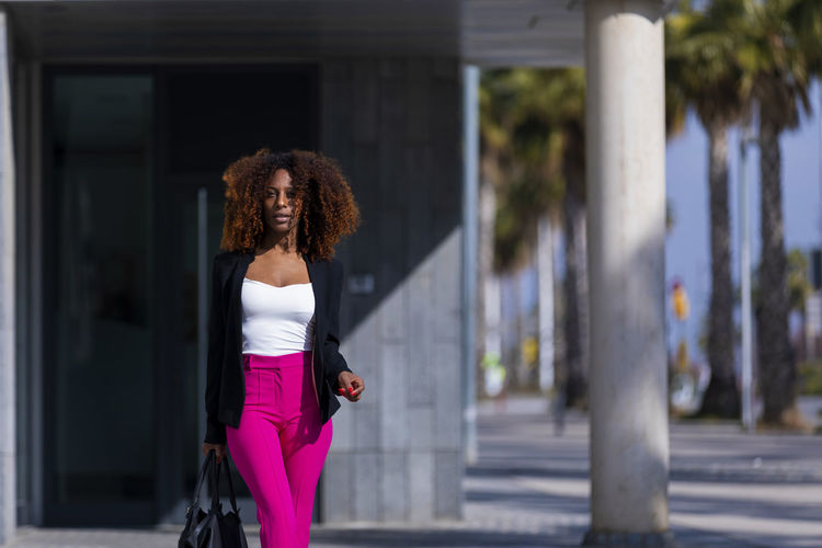 Front view of a young beautiful curly woman wearing elegant clothes and handbag while standing in the street in sunny day Curly Hair Hairstyle One Person Architecture Young Adult Women Young Women Lifestyles Hair Day City Focus On Foreground Built Structure Real People Building Exterior Standing Leisure Activity Adult Casual Clothing Frizzy Fashion Outdoors Beautiful Woman Architectural Column Woman African American Afro Denim Happiness Happy Fun Daylight Sunlight