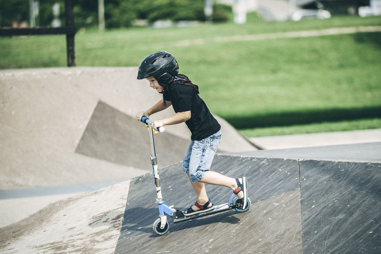 Side View Of Boy Riding Push Scooter On Sports Ramp In Park