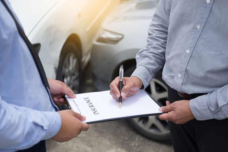 Midsection of customer signing on insurance paper with man
