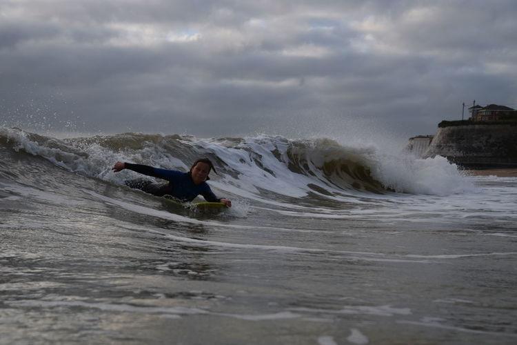 Woman surfboarding on waves in sea against sky