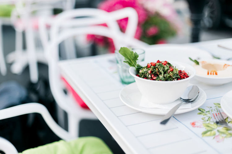 On the table in an arab restaurant there is a parsley tabbouleh salad with pomegranate seeds.