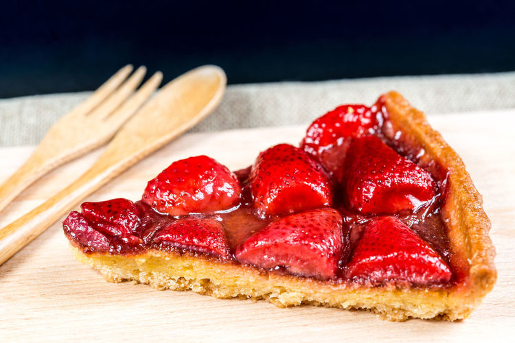 High Angle View Of Strawberry Tart Slice On Cutting Board