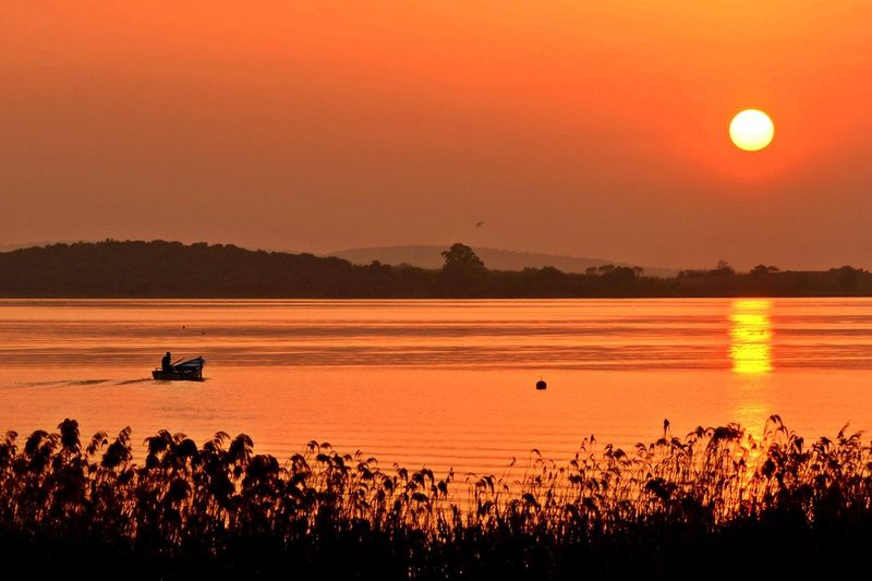 Person on boat in lake against orange sky