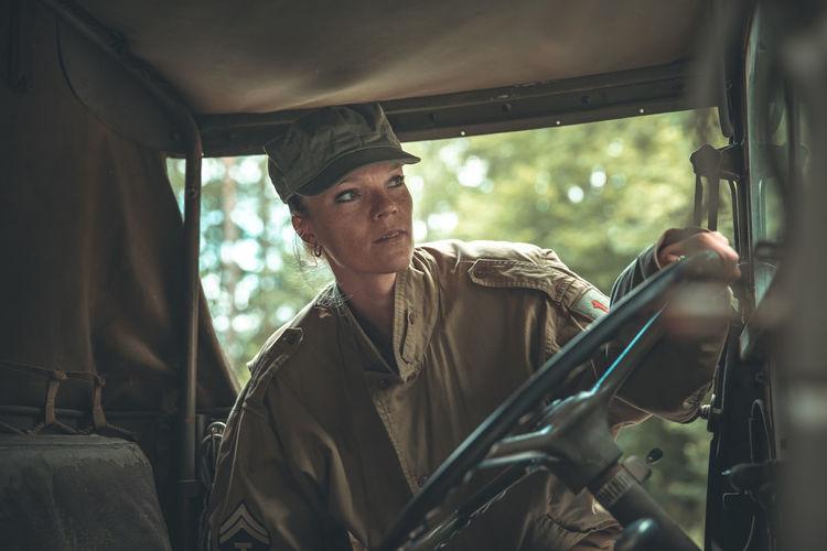 Woman soldier holding steering wheel of car
