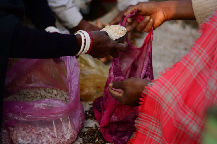 Midsection of man putting food in bag held by customer