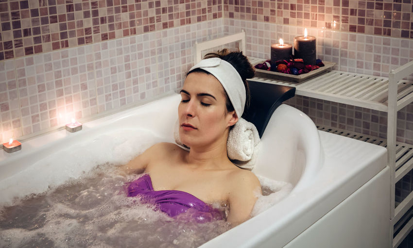 Young Woman With Eyes Closed Lying In Bath Tub At Home