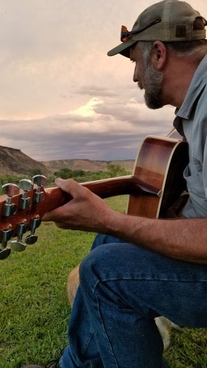 Side view of man playing guitar while sitting on land during sunset