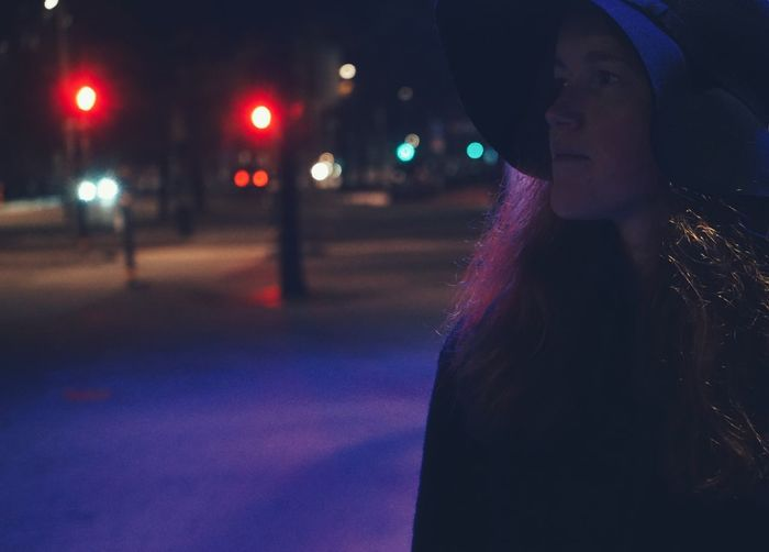 Portrait of young woman looking away in city at night