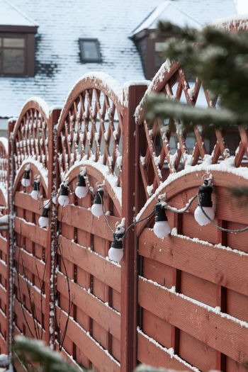 Wooden garden fencing hung with LED lights Fir Tree Garden Fence Latice Board Lighting Decoration Rooftop Day Dormer Windows No People Outdoors Posts Snow