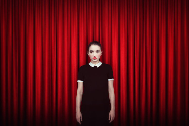 Adult Arts Culture And Entertainment Concept Curtain Front View Indoors  Looking At Camera Minimalism People Performance Portrait Red Serious Stage Stage - Performance Space Stage Theater Standing Studio Shot Waist Up Well-dressed Young Adult