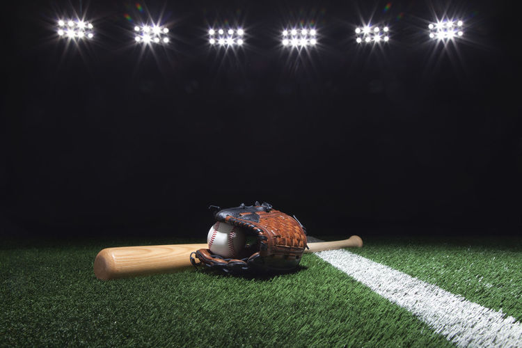 Baseball, mitt and bat on field under lights at night Baseball Bat Field Grass Leather Lights Low Angle View Stadium Wood Copy Space Dark Background Glove Mitt Night No People Photography Sports Sports Equipment Spot Lighting Team Sport