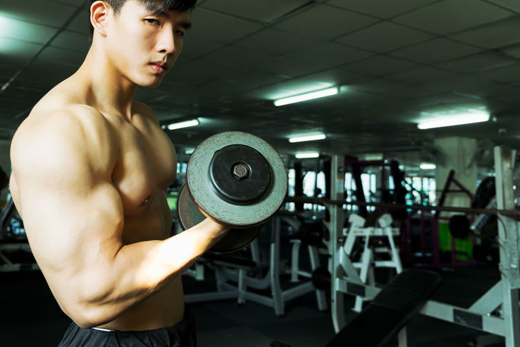Shirtless Muscular Man Lifting Dumbbell While Exercising At Gym