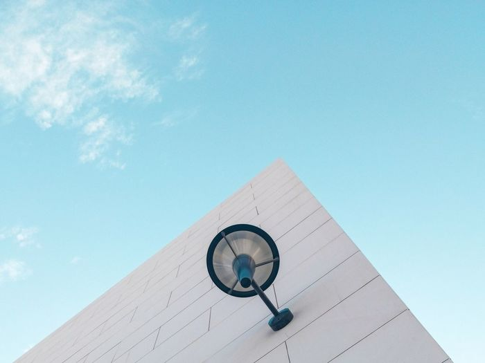 Low angle view of lighting equipment on wall of building against blue sky