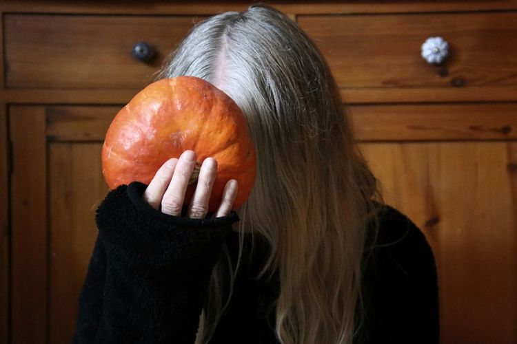 Close-up of woman holding pumpkin against wall