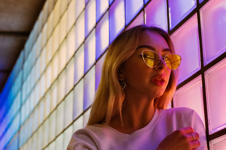 Illumination Beautiful Woman Eyeglasses  Females Front View Glass Glasses Hairstyle Headshot Indoors  Leisure Activity Lifestyles Looking Neon Neon Lights Nightlife One Person Portrait Purple Real People Sunglasses Wall - Building Feature Window Women Young Adult Young Women