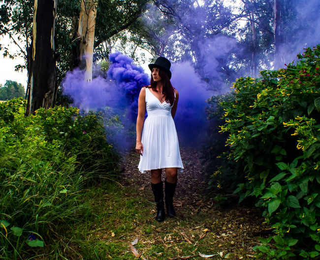 Full length portrait of young woman casting purple mist