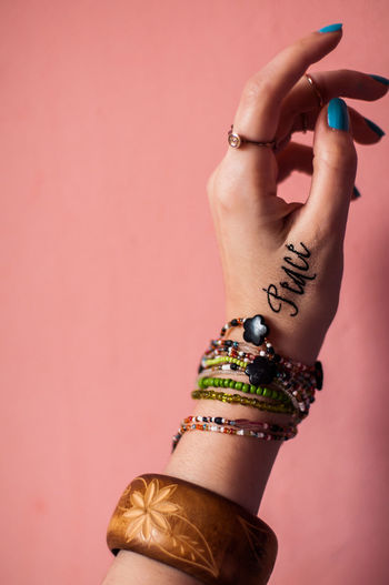 Cropped Hand Of Woman With Bracelets By Peach Wall