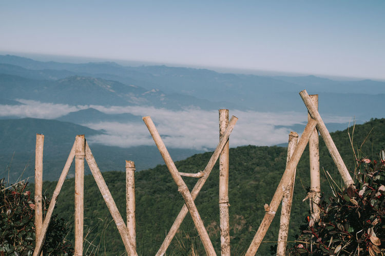 Wooden fence on mountain against sky