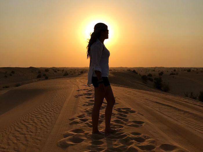 Man standing on sand dune in desert against sky during sunset