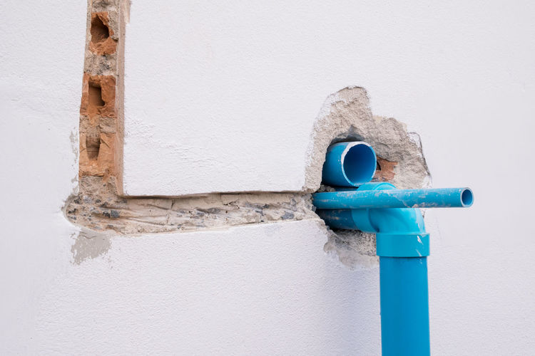 Close-up of blue pipe against white wall