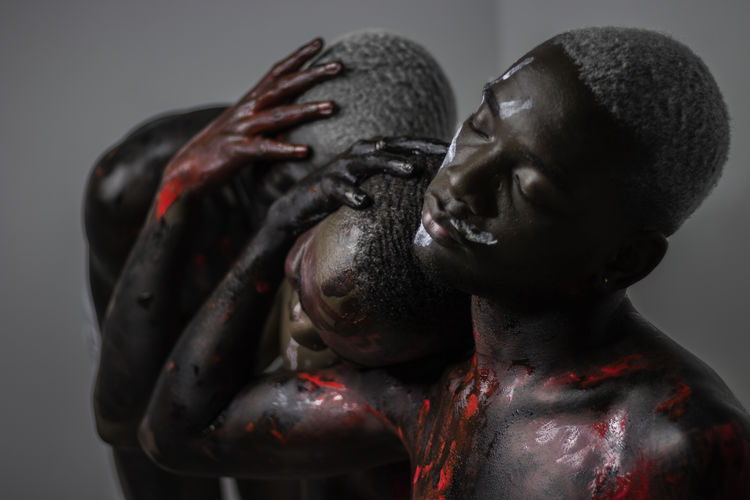 Young men with body paints resting head on shoulder
