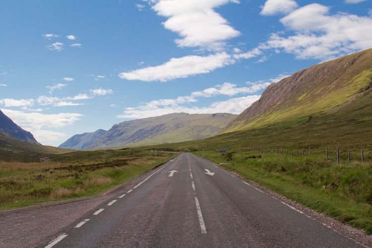 Scenic view of road and mountains against sky