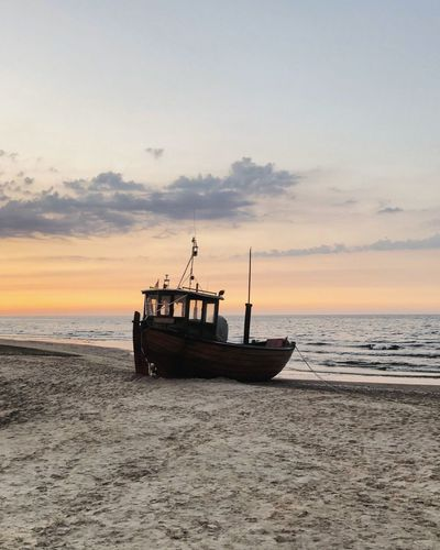 Fishing boat on beach against sky during sunset