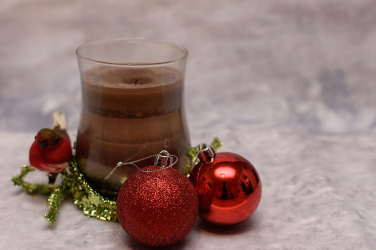 Close-Up Of Drink With Christmas Baubles On Table