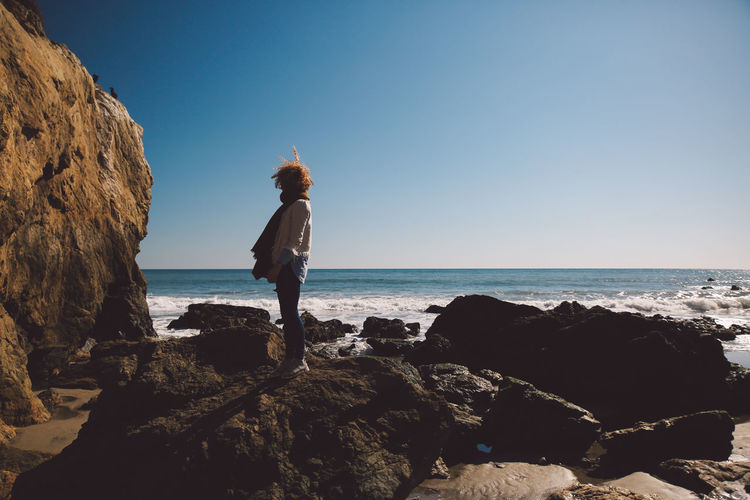 Side view of mid adult woman standing on rocky shore against sky