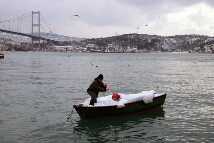 Fisherman on his boat filled with snow in Ortaköy Adult Bird Boat Full Of Snow Bosporus Bosporus Bridge Bosporus Fisherman Fisherman Boat Little Boat Little Fisherman Boat Lots Of Snow Nautical Vessel Outdoors Snow Covered Snow In The Boat Travel Destination Istanbul Water Winter At The Bosporus Winter Day Winter Landscape Winter Sky