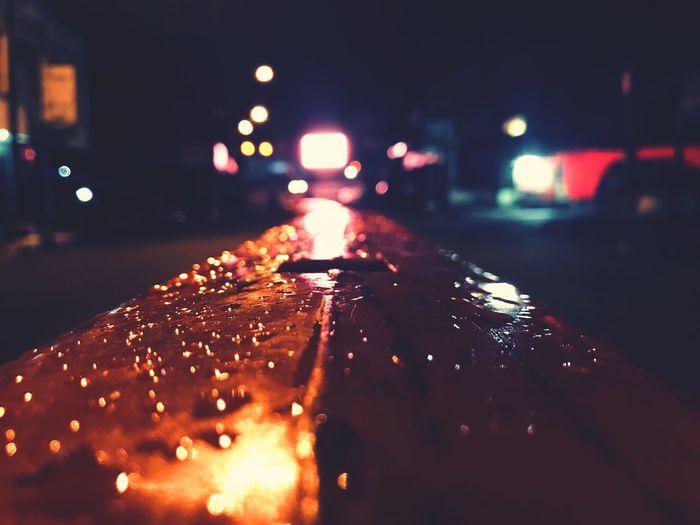 Close-up of wet illuminated street lights