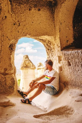 Kapadokya Cappadocia/Turkey Cappadocia Man Boy EyeEm Selects Full Length Sitting Sand Dune Sand Desert Beach Ancient Civilization Arch Shadow Sky Natural Arch Stalactite  Rock Formation Geology Eroded Physical Geography Canyon Moab  Limestone Civilization Old Ruin Visiting Amphitheater Rugged