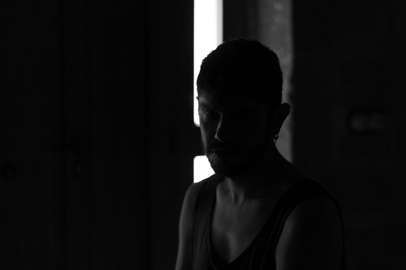 Portrait of shirtless man standing in darkroom