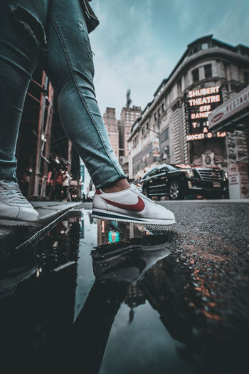 Low section of man standing on puddle in city