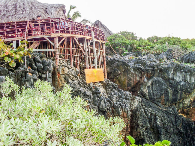 A small restaurant built on a cliff in the Dominican Republic Architecture Building Exterior Built Structure Clear Sky Cliff Day Green Nature No People Outdoors Restaurant Rickety Rock Formation Rural Scaffolding Sky Stone Stone Material Tranquil Scene Tranquility