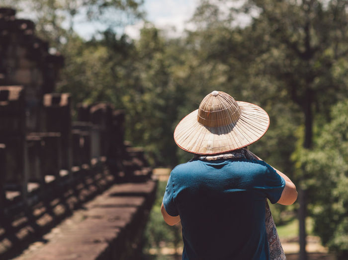 Rear View Of Man Wearing Hat Standing In Park During Sunny Day