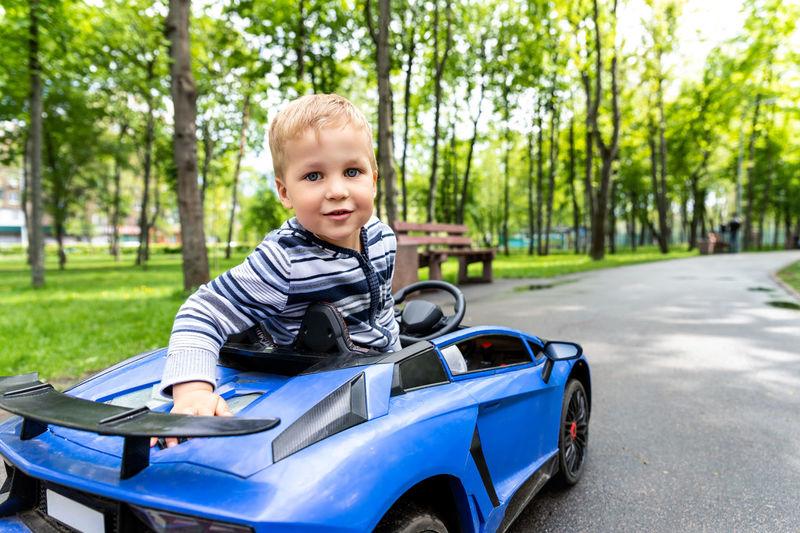 Portrait of boy sitting in electric toy car