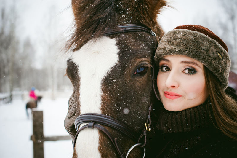 Close-Up Portrait Of Beautiful Woman With Horse During Snowfall