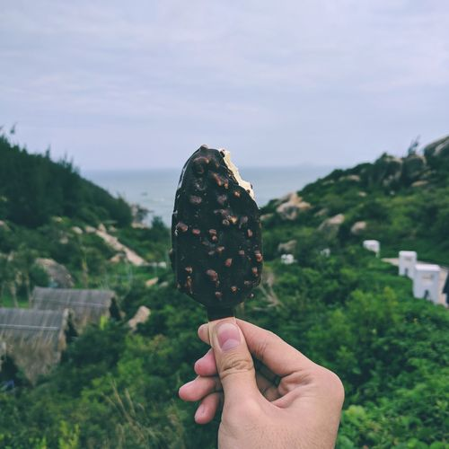 Close-up of hand holding ice cream against sky